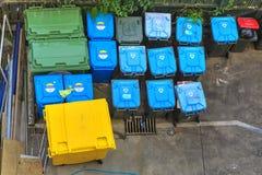Massor av plast- soptunnor/rackar ner på fack i en gränd, från över Arkivfoto