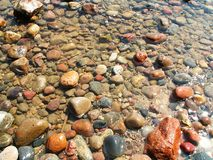Massor av skinande stenar i vatten på havet Royaltyfri Bild