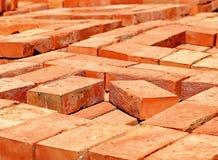 Massor av staplade nya röda tegelstenar Arkivbild