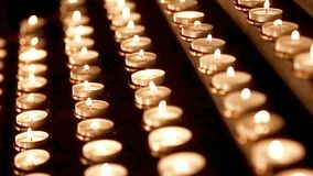 Massor av stearinljus med grunt djup Små stearinljus på tabellen i katolsk kyrka