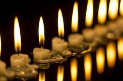 Massor av stearinljus som bränner i mörkret Arkivbilder