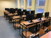 Massor av tabeller, datorer och bildskärmar i det tomma klassrumet arkivfoton
