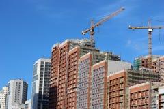 Massor av tornkonstruktionsplats med kranar och byggnad med bakgrund för blå himmel arkivbild