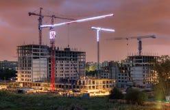 Massor av tornkranar bygger bostads- byggnader på aftonen Arkivbild