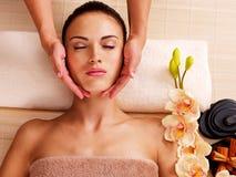 Massör som gör massage huvudet av en kvinna i brunnsortsalong Arkivfoton