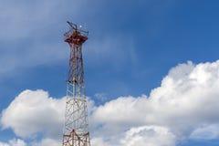 Mast av den cell- kommunikationen på en bakgrund av vita moln arkivfoton
