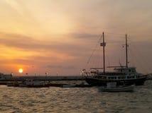 Mast av segelbåten mot härlig solnedgånghimmel över den gamla porten av Mykonos Arkivfoto