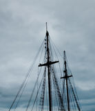 Mast of a caravel over a cloudy sky. Royalty Free Stock Photography