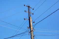 Mast electrical power line against blue sky Stock Image