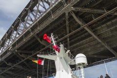 Mast för kryssningskepp omkring som passerar under Sydney Harbour Bridge Arkivbild