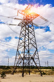 Through a mast of a high voltage cable for electricity, the sun shines Royalty Free Stock Photography