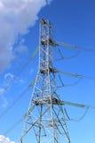 Mast la línea eléctrica eléctrica en un campo de trigo en un día soleado Imagenes de archivo