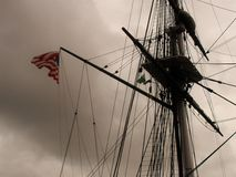 Mast on Old Schooner with Flag Flying in the Wind on a Rainy Day Stock Photography