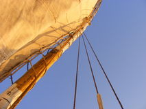 Mast of a sailing boat and blue sky. Sails on a small ship, simple photo of blue sky and a mast of a sailing boat on the river at sunset, simple beautiful stock Royalty Free Stock Image