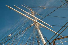 Mast of sailing ship. Image of mast from old sailing ship. Ropes go criss-cross and ladder goes to the top. Blue sky in the background stock photography