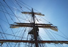 Mast and sails. Bottom view of mast, sails and rigging of an old sailing boat with sun partly hidden behing the mast against a blue sky with some clouds Stock Photography