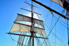 Mast, sails and rigging. The sun rises behind mast and sails from a sail boat in port Stock Photography