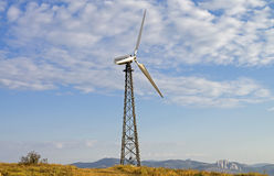Mast with wind power generator on the background of sky. Royalty Free Stock Photo