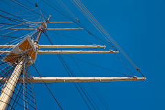 Mast of a wind-powered vessel. View at the top of the old sailing ship mast, yards and rigging. Against the blue sky Stock Images