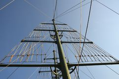 Mast on a yacht with a lot of ropes against a sunny blue sky on a summer day royalty free stock image