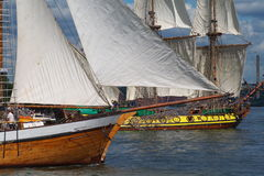 Masted sailing ships. Two old masted sailing ships or boats with coastline in background stock photography