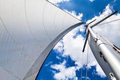 Masten och seglar mot himlen med moln Arkivbilder