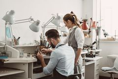 Master and apprentice. Young male assistant and female jeweler are working together at jewelry making workshop. Business stock photos