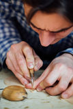 Master artisan luthier working on the creation of a violin. painstaking detailed work on wood. Stock Image