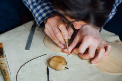 Master artisan luthier working on the creation of a violin. painstaking detailed work on wood. Master artisan luthier working on the creation of a violin royalty free stock images