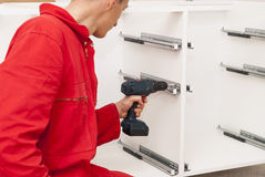 Master assembles furniture. Master with screwdriver in hand assembles furniture Royalty Free Stock Photo