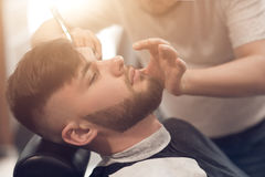 A master in the barbershop works with the client. Shaves beard young guy. shaving with a straight razor Stock Photography