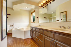 Master bathroom interior with brown cabinets, large mirror with lights and white bathtub. Has hardwood floor and vaulted ceiling Stock Photos