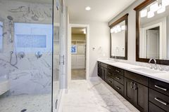 Master bathroom interior with double vanity cabinet. Bright and airy master bathroom features White Modern Double Vanity With Rich Brown Cabinets and marble walk royalty free stock photo