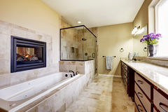 Master bathroom in modern house with fireplace and tile floor stock photos