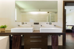 Master bathroom with two sinks and mirror. Master bathroom with two sinks, large mirror and wooden cabinet Royalty Free Stock Photos
