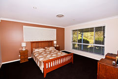 Master Bedroom. A master bedroom in a country home with a view to the forest outside Stock Images