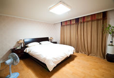 Master bedroom. Elegant master bedroom with window curtains and fan royalty free stock photo