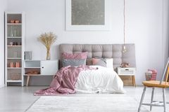 Master bedroom with buttoned headboard. Spacious cozy master bedroom interior with copper decorations on the white rack, wooden chair and buttoned gray headboard Stock Photos
