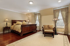 Master bedroom with cherry wood flooring Stock Photography