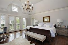 Master bedroom with doors to balcony. Master bedroom in luxury home with doors to balcony royalty free stock photos