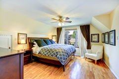 Master bedroom interior with beautiful queen size bed. And white armchair in the corner royalty free stock images