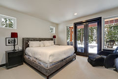 Master bedroom interior with queen size bed. And exit to spacious patio with hot tub. Northwest, USA stock image