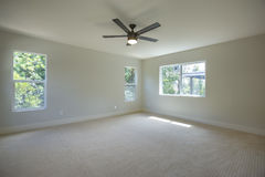 Master bedroom with light carpet and ceiling fan HDR stock images