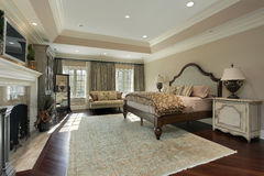 Master bedroom with marble fireplace. Master bedroom in luxury home with marble fireplace stock photography