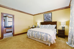 Master bedroom in pastel yellow tones with queen size bed Royalty Free Stock Photos