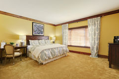 Master bedroom in pastel yellow tones with queen size bed Stock Photo