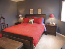Master Bedroom in Red 03. A modern master bedroom. Queen sized bed with red covers royalty free stock photography