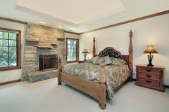 Master bedroom with stone fireplace Stock Photography