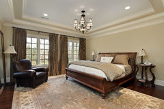Master bedroom with tray ceiling. Master bedroom in luxury home with tray ceiling royalty free stock images