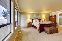 Master bedroom wtih beige walls and wood bed. Stock Photos